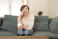 De jonge aantrekkelijke en gelukkige rode van de de zittings de laag thuis bank van de haarvrouw het drinken koffie die op mobiel Royalty-vrije Stock Foto's