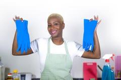 De jonge aantrekkelijke en gelukkige zwarte Afrikaanse Amerikaanse keuken die van het vrouwen schoonmakende huis en blauwe was ru royalty-vrije stock foto's