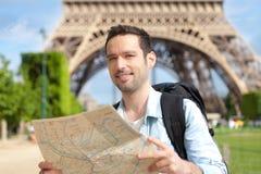 De jonge aantrekkelijke kaart van de toeristenlezing in Parijs stock foto's