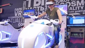 De jonge aantrekkelijke knappe kerel berijdt een motorfiets in virtuele werkelijkheid De vakantie, innovatie, het scherm, neon, f stock video
