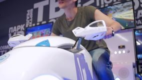De jonge aantrekkelijke knappe kerel berijdt een motorfiets in virtuele werkelijkheid De vakantie, sluit omhoog been, het verkort stock videobeelden