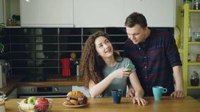 De jonge aantrekkelijke krullende gelukkige Kaukasische vrouw zit in keuken die iemand via smartphone texting, komt haar echtgeno stock footage