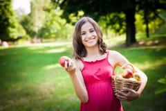 De jonge aantrekkelijke mand van de vrouwenholding met appelen, tegen groen stock foto's