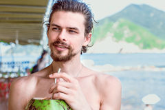 De jonge aantrekkelijke mens drinkt sap van groene kokosnoot en het kijken weg op de achtergrond van de baai en de bergen Royalty-vrije Stock Afbeeldingen