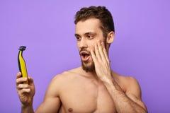De jonge aantrekkelijke mens is gelukkig om positief effect tijdens het scheren te hebben royalty-vrije stock afbeeldingen