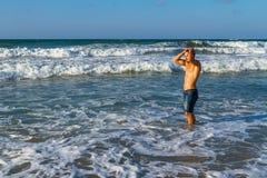 De jonge aantrekkelijke mens geniet van spalshing in oceaan Stock Fotografie