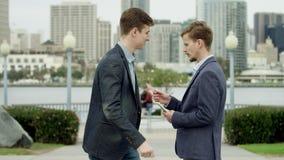 De jonge aantrekkelijke mens koopt een creditcard op een stoep in Coronado stock footage