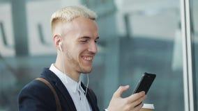 De jonge aantrekkelijke mens loopt onderaan de koffie van de straatholding en het gebruiken van telefoon Hij luistert aan muziek  stock videobeelden
