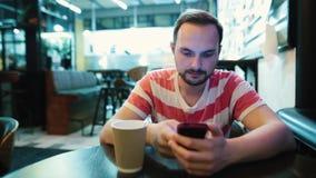 De jonge aantrekkelijke mens met een baard gebruikt een smartphone in een koffie stock footage