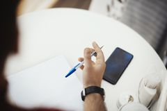 De jonge aantrekkelijke mens schrijft nota bij het document royalty-vrije stock afbeeldingen