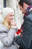 De jonge aantrekkelijke mens stelt huwelijk aan zijn liefde voor Stock Afbeeldingen