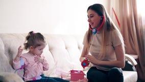 De jonge aantrekkelijke moeder en de zoete dochter spelen de rol van arts en patiënt stock video