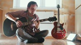 De jonge aantrekkelijke musicus speelt de gitaarzitting op de vloer in de keuken stock footage