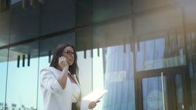 De jonge aantrekkelijke onderneemster spreekt op telefoon, in openlucht lopend langs de bureaubouw stock footage