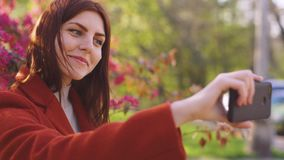 De jonge aantrekkelijke roodharige vrouw maakt een selfie op de achtergrond van de lentebloemen van kers of sakurabloesems op sma stock videobeelden