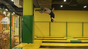 De jonge aantrekkelijke sportieve atleet voert voorsalto mortales en lichaams twistsat professionele trampoline voor opleiding ui stock footage