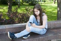 De jonge aantrekkelijke telefoon van het meisjesgebruik op bank Het park van de zomer foto Royalty-vrije Stock Fotografie