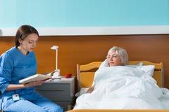 De jonge aantrekkelijke verpleegster in eenvormig leest een boek voor haar pati Royalty-vrije Stock Afbeelding