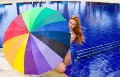 De jonge aantrekkelijke vrouw bij pool onder kleurenu Stock Afbeelding