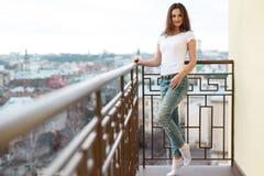 De jonge aantrekkelijke vrouw die vrijetijdskleding dragen stelt op het balkon van de luxebouw Royalty-vrije Stock Afbeeldingen