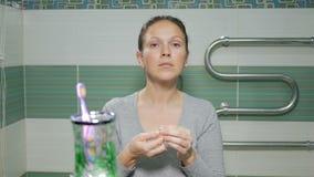 De jonge aantrekkelijke vrouw draagt pareloorringen in de badkamers van de hotelruimte stock video