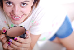 De jonge aantrekkelijke vrouw drinkt koffie stock afbeelding