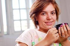 De jonge aantrekkelijke vrouw drinkt koffie royalty-vrije stock afbeeldingen
