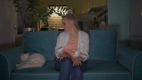 De jonge, aantrekkelijke vrouw gaat zitten met een mok op een bank aan kat en zet de televisie aan gebruikend een afstandsbedieni stock footage