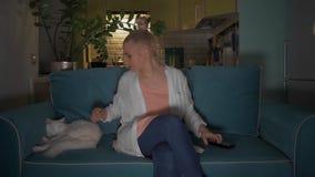De jonge, aantrekkelijke vrouw gaat zitten met een mok op een bank aan kat en zet de televisie aan gebruikend een afstandsbedieni stock video