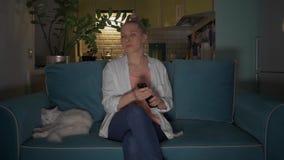 De jonge, aantrekkelijke vrouw gaat zitten met een mok op een bank aan kat en zet de televisie aan gebruikend een afstandsbedieni stock videobeelden