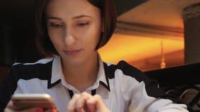 De jonge Aantrekkelijke vrouw gebruikt haar mobiele telefoon in een comfortabel koffierestaurant Zij glimlacht en gelukkig stock videobeelden