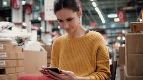 De jonge aantrekkelijke vrouw in het oranje jasje gebruikt een smartphone, zittend onder de dingen in een opslag stock video