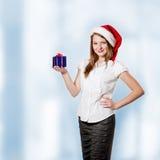De jonge aantrekkelijke vrouw houdt Kerstmisgift Royalty-vrije Stock Afbeeldingen