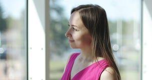De jonge aantrekkelijke vrouw kijkt in een groot venster stock video