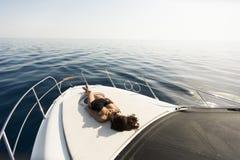 De jonge aantrekkelijke vrouw ligt en zonnebadend op de boog van een luxejacht stock fotografie