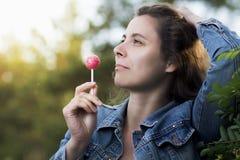 De jonge aantrekkelijke vrouw likt karamelsuikergoed op een ijskegel op sti stock afbeelding