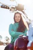 De jonge aantrekkelijke vrouw met gekruiste handen zit op rode motorfiets Royalty-vrije Stock Foto