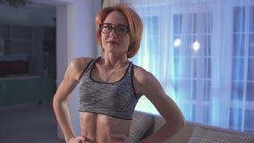 De jonge aantrekkelijke vrouw met kort rood haar in glazen zet thuis op sportbovenkant Het meisje toont haar gepompte buik stock video