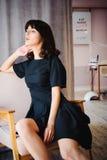 De jonge aantrekkelijke vrouw met lange benen in zwarte elegante kleding, zit als voorzitter dichtbij venster in binnenland van r Stock Afbeelding