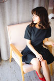 De jonge aantrekkelijke vrouw met lange benen in zwarte elegante kleding, zit als voorzitter dichtbij venster in binnenland van r Royalty-vrije Stock Afbeeldingen