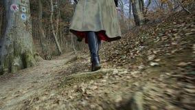 De jonge aantrekkelijke vrouw met rode hoed wandelt in bos stock footage
