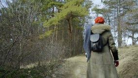De jonge aantrekkelijke vrouw met rode hoed wandelt in bos stock video