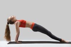 De jonge aantrekkelijke vrouw status in Stijgende Plank stelt, grijze studi stock fotografie