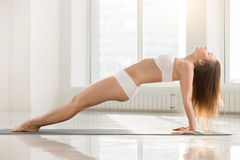 De jonge aantrekkelijke vrouw in Stijgende Plank stelt, witte kleurenbackgro stock fotografie