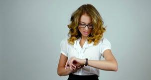 De jonge aantrekkelijke vrouw verschijnt en bekijkt haar horloge, kijkt aan een celtelefoon en gaat dan weg stock footage