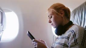 De jonge aantrekkelijke vrouw vliegt in een vliegtuig Het gebruikt een smartphone luisterend aan muziek stock video