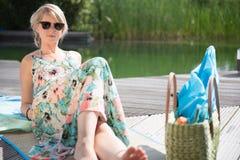 De jonge aantrekkelijke vrouw zit bij de pool Stock Afbeeldingen