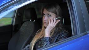 De jonge Aantrekkelijke Vrouw zit in een Geparkeerde Auto en zweert telefonisch stock video