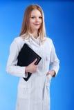 De jonge aantrekkelijke vrouwelijke arts bevindt zich met het klembord Stock Afbeeldingen