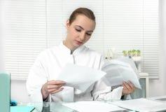 De jonge aantrekkelijke vrouwelijke wetenschapper of de gediplomeerde student lezen scie Stock Foto